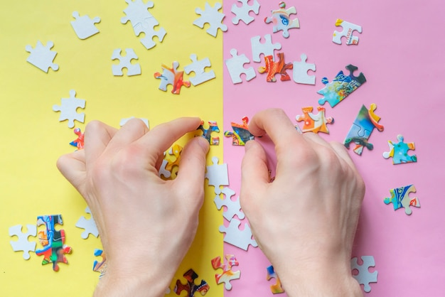 Overhead view o hands solving puzzle lat lay