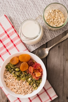 Overhead view of oats, dry fruits and pumpkin seeds in white bowl with milk on table