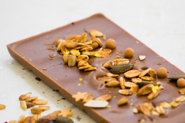 An overhead view of oats; seeds and dried fruits on chocolate bar