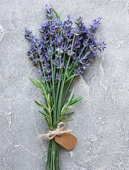 콘크리트 표면에 빈 태그가있는 신선한 라벤더 꽃 다발의 오버 헤드보기