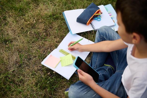 Вид сверху симпатичного умного школьника, который учится в парке, сидит на зеленой траве и решает математические задачи, используя смартфон и мобильные приложения, делая заметки в блокноте и рабочей тетради.