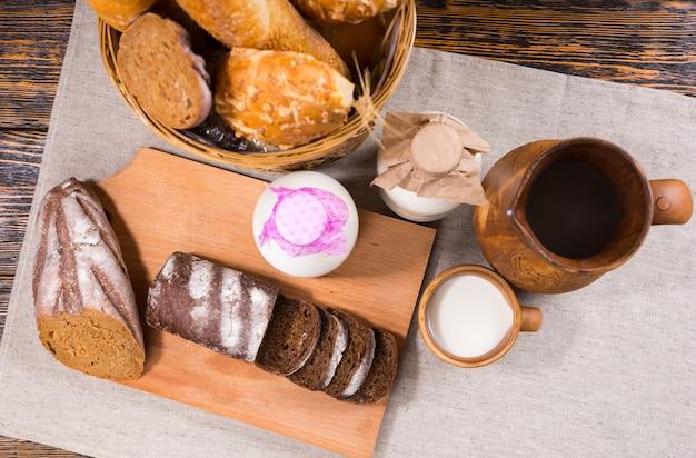 2つの牛乳瓶と木製の水差しの横にあるパンとスライスしたパンパーニッケルの豊富な品揃えの俯瞰図