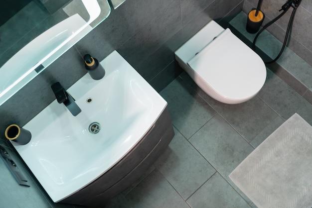 Вид сверху на интерьер современной монохромной ванной комнаты с единственным белым туалетным столиком и подвесным унитазом над серым плиточным полом с ковриком для ванной.