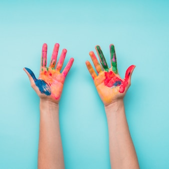 青い背景に塗られた手のオーバーヘッドビュー