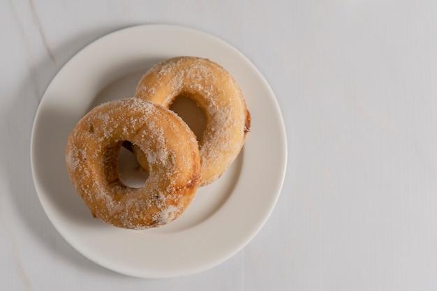흰색 컵이 있는 흰색 접시에 퍼지가 채워진 설탕 도넛 한 쌍의 머리 위