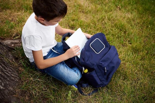 思春期前の男子生徒がバックパックからワークブックを取り出し、都市公園の緑の芝生に座って、屋外で宿題をする準備ができている様子の俯瞰図。野外で学校の仕事をしている愛らしい子供