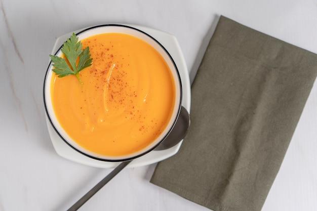 緑のナプキンにスカッシュとニンジンのスープのクリームと白いボウルの俯瞰図