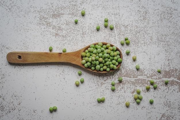 白い素朴なテーブルの上のエンドウ豆と木のスプーンの俯瞰図