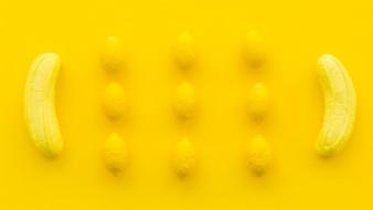 黄色の背景にバナナとレモンキャンディのオーバーヘッドビュー