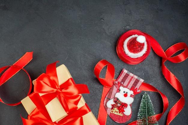 暗い背景の上の美しい贈り物とクリスマスソックスのクリスマスツリーサンタクロースの帽子の俯瞰図
