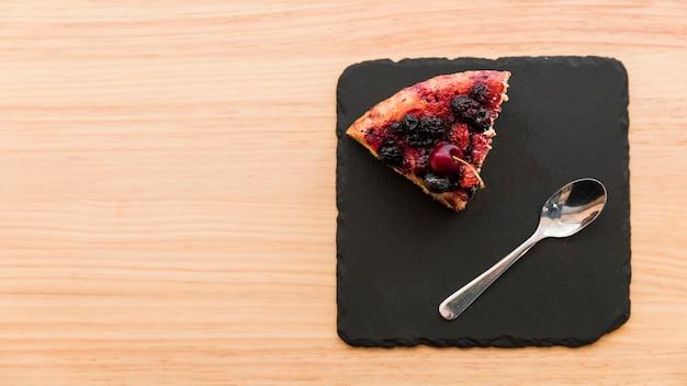 Верхний вид ягодного теста и ложки на доске сланца