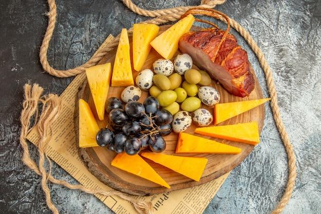 古い新聞の木製の茶色のトレイロープにさまざまな果物や食べ物と最高のスナックの俯瞰図