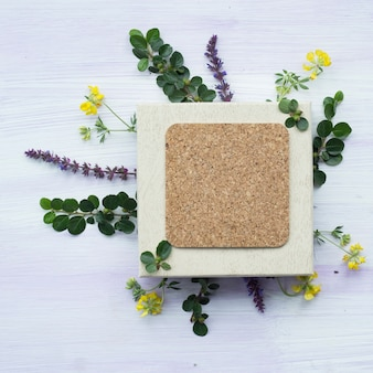 Overhead view of blank cork frame with lavender flowers and twig on wooden background