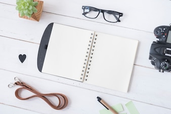Overhead view of blank spiral notepad; spectacle; belt; pen; heartshape; professional camera and succulent plant on white wooden table
