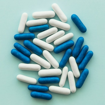 Overhead view of blue and white oval candies on colored background