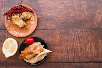Overhead view of boiled and roasted chicken with ingredients over wooden desk