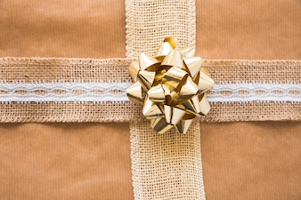 Overhead view of bow and weaving ribbon on brown gift paper