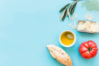 Overhead view of bread, oil, grated cheese and tomato on blue background
