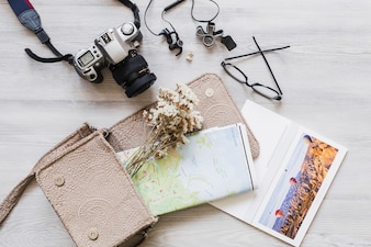 Overhead view of camera, handbag, and map on wooden desk