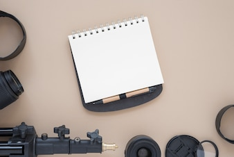 Overhead view of camera lens with tripod and blank notepad on colored background