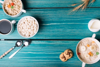 Overhead view of cereals, oatmeal with coffee and tea on turquoise table