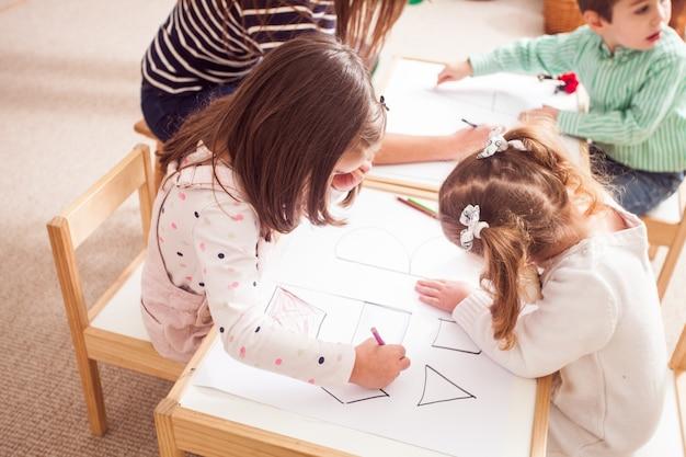 Вид сверху на детей в детском саду учат буквы и фигуры, раскрашивая их