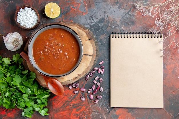 木製トレイの青いボウルスプーンで古典的なトマトスープの俯瞰図ガーリックソルトレモン緑の束と混合色のテーブルのノートブック
