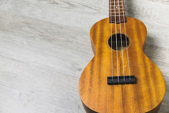 Overhead view of classical wooden guitar string on wooden plank backdrop