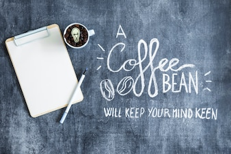 Overhead view of clipboard and mug with coffee beans on chalkboard with text