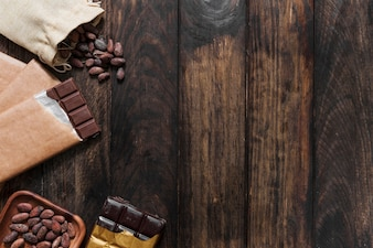 Overhead view of cocoa beans and chocolate bars on wooden table