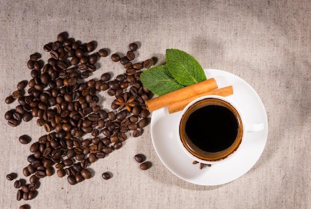 キャンバス上のマグカップによるコーヒー豆の山の俯瞰図