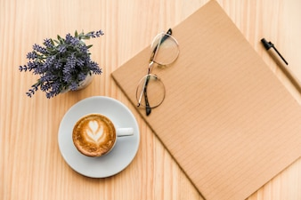 Overhead view of coffee latte,stationeries and lavender flower on wooden background