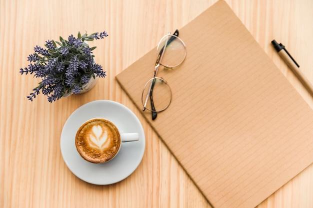Верхний вид кофе латте, канцелярские принадлежности и цветок лаванды на деревянном фоне