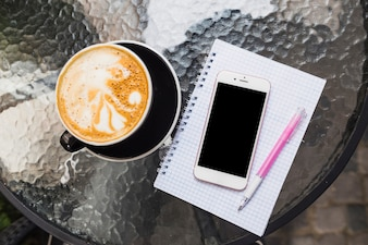 Overhead view of coffee with mobile phone on checked notebook and pen
