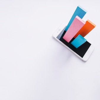 Overhead view of colorful bars popping out from smartphone screen on white backdrop