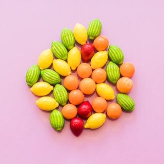 ピンクの背景にカラフルなフルーツの形のキャンディのオーバーヘッドビュー