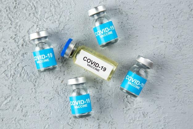 Covid-백신의 오버 헤드 보기는 여유 공간이 있는 회색 모래 배경에 있습니다.