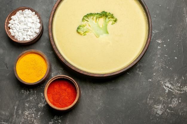 茶色のボウルにクリーミーなブロッコリースープと灰色のテーブルにさまざまなスパイスの俯瞰図