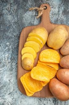 회색 테이블에 나무 커팅 보드에 바삭한 칩과 생 쌀된 감자의 오버 헤드보기