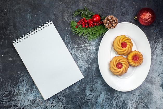 白いプレート上のおいしいビスケットとノートブックの暗い表面の横にある新年の装飾の俯瞰図