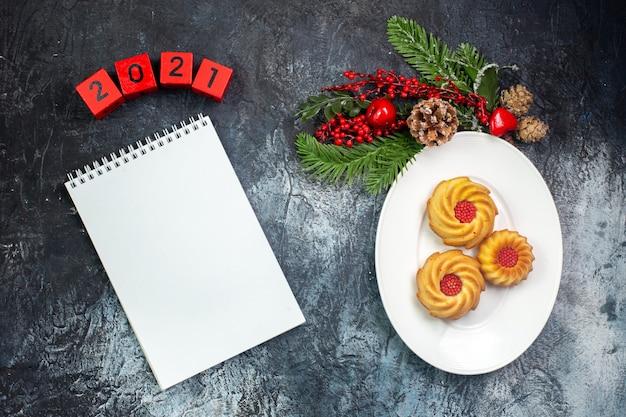 白いプレートと新年の装飾のおいしいビスケットの俯瞰図サンタクロースの帽子番号次のノートブック暗い表面