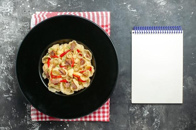 皿に野菜と緑、赤いストリップタオルにナイフと灰色の背景にノートブックとおいしいコンキリエの俯瞰図
