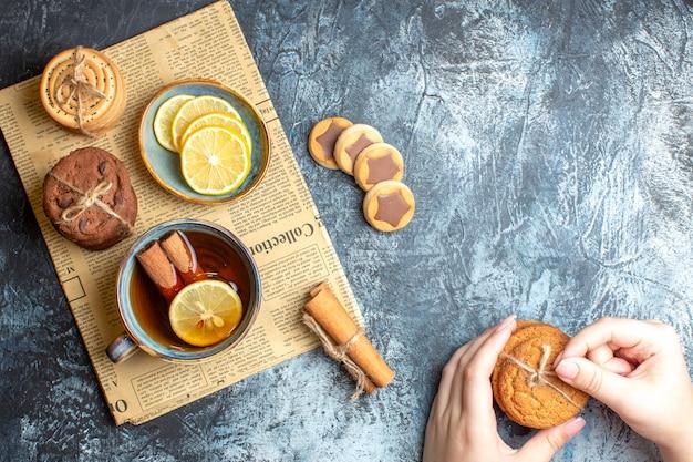 暗い背景に古い新聞にシナモン入りの紅茶のカップを持つおいしいクッキーと手の俯瞰