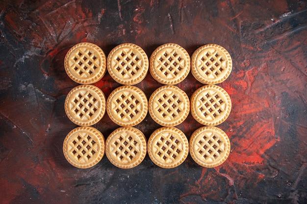여유 공간이 있는 혼합 색상 배경에 행으로 배열된 맛있는 쿠키의 오버헤드 보기