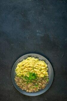 Вид сверху вкусного ужина с картофельным пюре и мясом на тарелке на черном фоне со свободным пространством