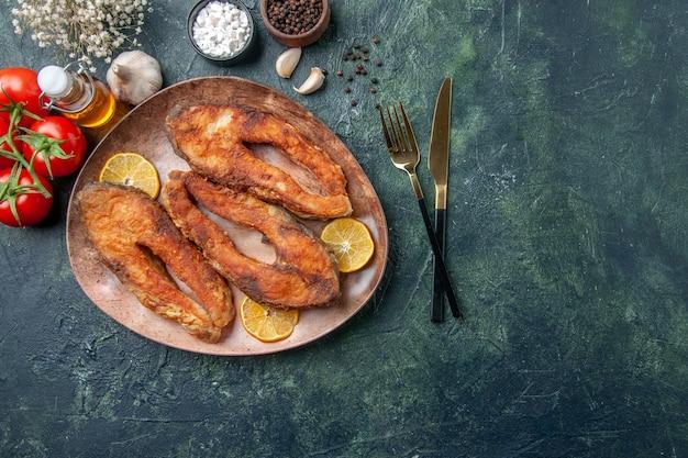 茶色のプレートにおいしい揚げ魚とレモンスライスの俯瞰図スパイストマトオイルボトルのミックスカラーテーブルに空きスペースがあります