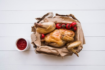 Overhead view of delicious grilled chicken in brown paper with tomato sauce over wooden table