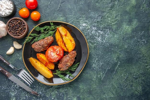 검은 접시에 감자와 토마토로 구운 맛있는 고기 커틀릿의 오버 헤드 보기는 오른쪽에 향신료 마늘 토마토를 설정합니다.