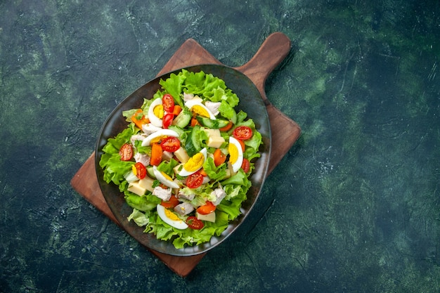Вид сверху на вкусный салат со множеством свежих ингредиентов на деревянной разделочной доске на фоне черно-зеленого микса