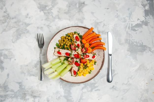 Вид сверху на вкусный салат с различными ингредиентами на тарелке и набор столовых приборов на белой поверхности со свободным пространством